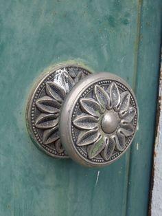Beautiful doorknob for a vintage interior design bathroom.   green door