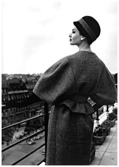 Katherine Pastrie in grey flannel suit with the jacket's belted waist accentuating the full sleeves, cloche in black felt with grey flannel band, Crahay for Nina Ricci, 1959,Paris    Photo Willy Maywald