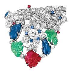 Diamond and Carved Colored Stone Pendant-Brooch – Doyle Platinum, topped by a stylized branch and flower centering one old European-cut diamond approximately .60 ct., set throughout with 42 old European and single-cut diamonds approximately 2.25 cts., accented by 9 small round sapphires and rubies, embellished by 5 carved emerald, sapphire and ruby leaves, circa 1935,