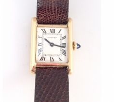 Cartier Lady's 18K Yellow Gold Tank Quartz Wrist Watch, 28mm x 20.5mm case, white dial, roman numerals, sapphire winding stem, and leather strap.  Good Condition   One year guarantee on movement only!!! Item Number: WOO859