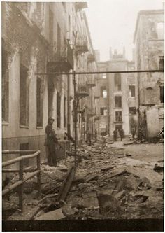SS troops search ruined buildings for survivors during the suppression of the Warsaw Ghetto Uprising.