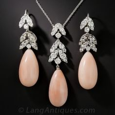 Ultra-sparkling, foliate design, platinum and diamond-set tops culminate in sizable and lustrous pretty pink coral drops in this stunning earrings and necklace suite dating from the 1950s-60s. 4.25 carats of bright white round brilliant-cut diamonds sparkle from within navette, or leaf shape settings. The earrings measure 1 7/8 inches and drop a bit lower from the ear wires; the pendant measures just over 2 inches. Fabulous feminine mid-century jewels.
