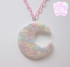 """☆ moon necklace with pastel stars  ☆ made from resin, glitter, paint, pastel stars and sprinkles ☆ chain: pink plastic chain  ☆ moon size: 7 cm x 7 cm (2.7"""" x 2.7"""")  ☆ chain length: 58 cm (22.8"""")  ☆ moon has a creamy color background with lots of pastel stars and sprinkles ☆ handmade necklace"""