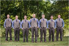 Groom and Groomsmen in gingham blue button up shirts with brown pants and wool vests.