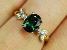 Ovular gem with cluster set diamonds alongside it