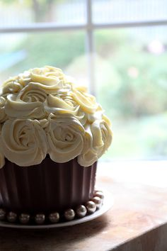 I want my wedding cake to be inspired by this cupcake. Chocolate frosting with beautiful cream or colored flowers. Definitely a different take on your traditional white cake.