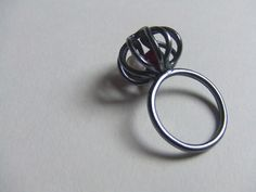 CO2 charm ring.  Freshwater pearls and garnets trapped inside an oxidised silver cage.    Elizamar jewellery by Jody Cornett