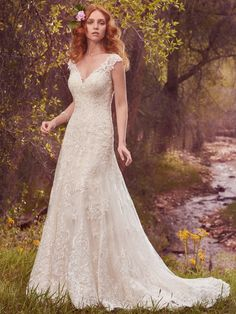 Maggie Sottero - TABRETT, This shimmering sheath wedding dress features a layer of delicate lace appliqués over a layer of allover lace. Lace appliqués adorn the illusion cap-sleeves, illusion sweetheart neckline, and illusion back with keyhole opening. Finished with covered buttons over zipper closure.