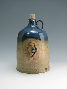 Wheel thrown jug. Cone 10 stoneware. Reduction fired. A torch was used to crack the outside of the jug, then the face was sculpted and pressed through the crack from the inside.