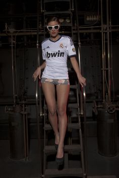 Real Madrid girl high above the ground showing off the white jersey. White fashionable sunglasses and a machine background completes the scenery.