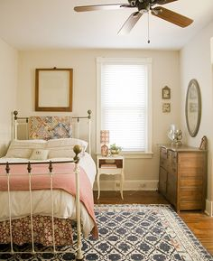 lovely guest room - I like the mix of prints with white bedding. Pink/red gingham blanket, flowery-like bed skirt (can make this easily), and blue accents. Little antique frames on wall with oval mirror. Could dress it up more with garden-themed prints, my sketches or photos from our garden.