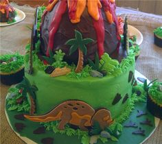 """I made this cake for my son's Dinosaur themed 3rd Birthday party. I used the Dinosaur Tracks cartridge to cut out a few dinos, footprints and palm trees out of fondant and modeling chocolate and then """"glued"""" them to toothpicks with melted chocolate so they """"stood"""" on the layers."""