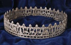 This Crown or Coronal is a copy of an original in the Cluny Museum, Paris. There are several styles of these segmented crowns suggesting that they were a popular item for pilgrims. The originals were made in a lead/tin alloy suggesting that they were not high status. This replica is in lead free pewter. The repeating panels are hinged so that the crown adjusts to the shape of the head. Each panel shows the Virgin and Child, the Three Wise Men on horseback and the Angel. This crown measures…