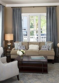 tan and blue living room/ like putting the curtain rod up by the ceiling