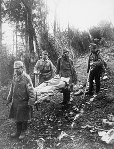 AUSTRO-HUNGARIAN CAMPAIGN AGAINST ITALY 1914 - 1918 (HU 57552)   Austrian wounded being carried down a screened road on the Alpine front. The first stretcher bearer is wearing a form of cap comforter over his field cap. The rear bearer is wearing another form of cap comforter in place of his field cap. The two other men are from an Alpine unit, probably the Edelweiss Division, and the man on the left is of Warrant Officer rank.