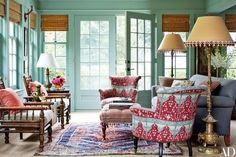 In the sunroom of a Long Island home renovated by designer Daniel Sachs and architect Kevin Lindores, a pair of barrel-back armchairs clad in a Brigitte Singh fabric flank a custom-made ottoman | archdigest.com