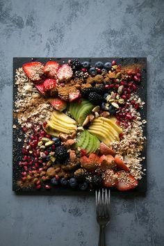Mango Kiwi fruit platter with pomegranates, blackberry, blueberry, coconut flakes, almond, pistachio, puffed quinoa, toasted oats, cinnamon, and poppy seeds