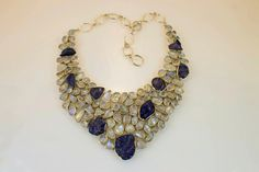 Rainbow Moonstone and rough Tanzanite in a sterling silver collar style necklace. An unusual arrangement of gems with the rough cut tanzanite among the smooth translucent moonstone. Tanzanite is blue/purple depending how light passes through its crystal orientation can appear violet/sapphire blue to burgundy.