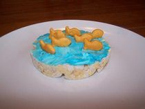 Rice cake  Cream cheese Food coloring Fish shaped crackers   Got this idea from :- http://kidscooking.about.com/od/snacksdipsappetizers/r/GoldfishRicecak.htm