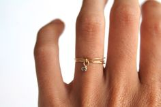 Three delicate 14k solid yellow gold rings with a 2mm White Diamond dangling charm by Lumo