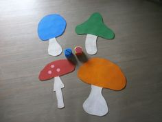 Wiskundige initiatie: Zelfgemaakt spel om met 4 kleuters te spelen. Je gooit eerst met de kleurendobbelsteen en daarna met de getallendobbelsteen. Je neemt het aantal stippen in de kleur dat je geworpen hebt en legt die op jouw paddenstoelenkaart. Wie er het eerst 20 heeft, is gewonnen.