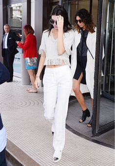 Kendall Jenner wears a cropped fringe sweater, wide-leg white pants, and slip on sneakers