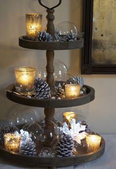 Repurpose a tiered cookie tower, add silvered cones, clear glass and tealights for a softly lit centrepiece
