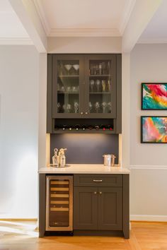 The new custom built-in dry bar with wine storage acts as a focal point for an existing entry which bisects the open space and defines the family room from the dining area.