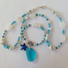 Gorgeous Seaglass And Swarovski Starfish Necklace.    This pretty blue sea themed necklace measures 23 inches in length.  It is made from