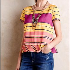 "Anthropologie Maeve Bennett Top Great top in a beautiful structured silhouette; looks like a tailored piece. Vibrant jewel tones in yellow-orange, magenta, and pink/coral colors that pop with the navy blue striping. Fabric is substantial & has a beautiful slight sheen. Unique detailing in the back with cross over that does not gape open as well as three small fabric-covered buttons. Fits true to size, 21"" long. Great year-round top. Worn once – in excellent condition & just dry cleaned…"