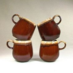 Here is a set of four McCoy coffee mugs, brown drip glazed, style 7025, made in the USA! Each mug is 4 tall and holds 12 ounces. No chips,