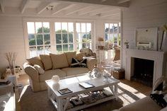 mur latté blanc, sol bois, table basse blanche, canapé beige, cheminée blanche, esprit bord de mer