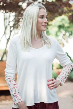 Feeling Floral Top from Sweetest Stitch Boutique  Soften your wardrobe with this fun, long sleeve waffle tee. Featuring a v-neck, flowing hem, and gorgeous floral sleeve detail, this sweet top is a dream. Model is wearing size Small.
