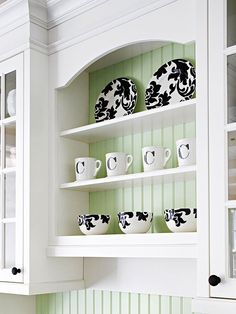 Pale green painted beadboard behind white painted open cabinet with shelves