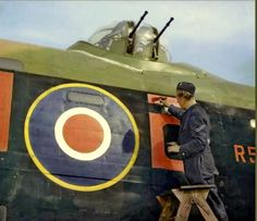 44 Sqn. Lancaster KM-o based in Waddington, Lincolnshire being touched up by a rigger. Until June 1942 these codes had been light grey, but were changed to dull red because it was  less conspicuous in moonlight.. The bar above the 'o' indicated the second 'O-Orange' in the squadron. This aircraft (R 5540) was written off in a crash-landing at Winthorpe in Jan. 1943.