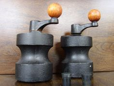 ROBERT WELCH A beautiful modernist pair of cast iron salt and pepper grinders with teak rounded handles and original rubber stoppers.