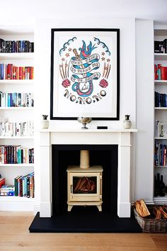 Tattoo art above fire place in living room with ceiling to floor bookshelves