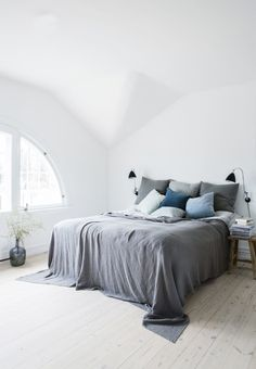 Minimalistic and nordic bedroom featuring a master bed with pillows and bedspread in soft tones.