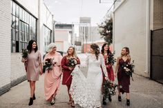 Fall rooftop wedding with lace bridal gown and mix and matched pink, red, burgundy bridesmaid dresses