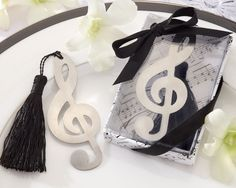 "Our stylish ""Timeless Duet"" Brushed-Metal Openwork Bookmark with Elegant Silk Tassel will surely add harmony to your special day! Each bookmark features a brushed-metal treble-clef elegantly designed in an openwork style, and finished with a classic black-silk tassel. Share your love of music with your family and friends, who won't forget the sweet love song the two of you have written. Size: Bookmark measures approximately 3 1/4"" h x 1 1/4"" w"