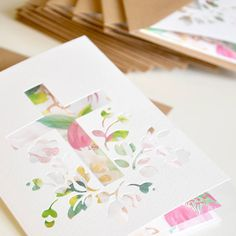 A beautiful papercut greeting card, perfect for christenings.Through the paper cut design, you get a glimpse of the gorgeous watercolour print. The print is a mix of hand painted tropical flowers in soft co-ordinating colours with a touch of gold accents. Once it's time to take down the welcome wishes, you don't throw this card away, oh no! These cards have been designed to become a treasured memento of the special day. Simply pop the card into a mounted picture frame and 'hey presto!' a…