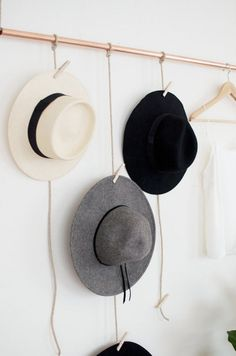 use a pipe, some twine, and clothes pins as an easy, creative, DIY way to hang hats!