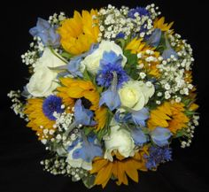 Hand tied bouquet created with sunflowers, cornflowers, blue delphinium, white roses, and babies breath.