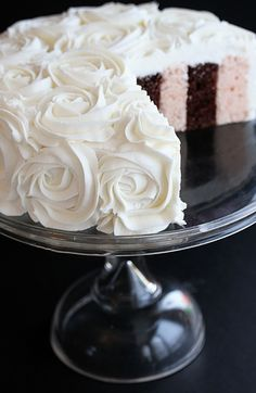 White rose cake with brown & pink stripes inside.