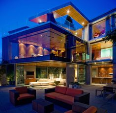 Comfy Outdoor Seating With Red Sofa And Armchair Also Rectangular Table On The Yard Of The Modern Open Floor Plan House With Glass Facade And Rectangular Shape In Sparkle Lighting Systrem