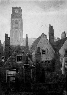 Gezicht op de achterzijde van de woonhuizen aan de Westewagenstraat in 1905. Op de achtergrond de toren van de Grote Kerk.  De Westewagenstraat komt reeds voor in 1363, evenals de Wagenbrug aldaar op het Westeinde. Later wordt ze ook Delftsche Wagenstraat genoemd, omdat ze de 'rijweg' was naar Delft. Hier hadden zich wagenverhuurders gevestigd, voer het wagenveer af en konden boeren en buitenlui , die de Delftsepoort waren binnengetreden, hun paarden stallen.