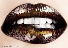 Dark brown lip color and shimmery gold lip gloss highlight.