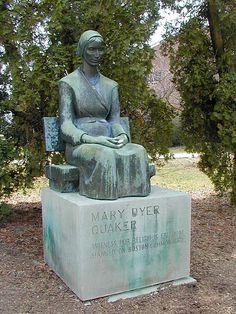 """A bronze statue of Mary Dyer who """"Hung as a flag"""" on Boston Commons,1 June 1660. By Quaker sculptor Sylvia Shaw Judson. She sits in front of the Massachusetts State House in Boston; a copy sits in front of the Friends Center in downtown Philadelphia, Pennsylvania, and another in front of Stout Meetinghouse at Earlham College in Richmond, Indiana."""