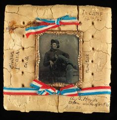 A preserved piece of American Civil War hardtack embedded with a tintype portrait of Union soldier Augustus Bigelow Hayes, which was taken after he was wounded at the Battle of Stones River while serving with the 1st Ohio Volunteer Infantry Regiment, c. 1862-1865.