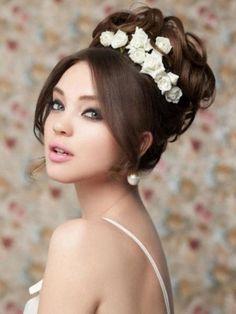 coiffure mariage: chignon haut bouclé et roses blanches